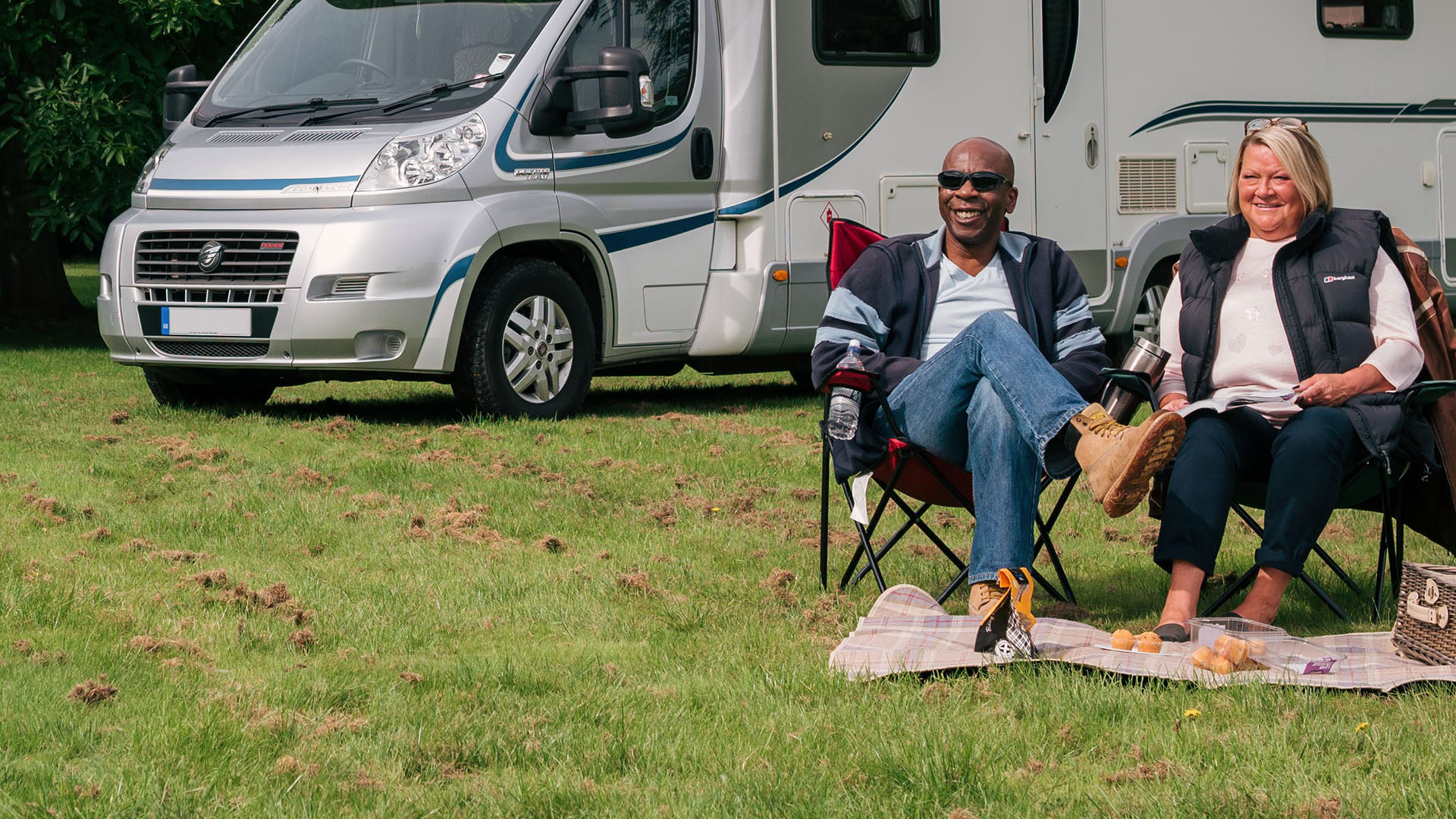Two people relaxing next to their motorhome