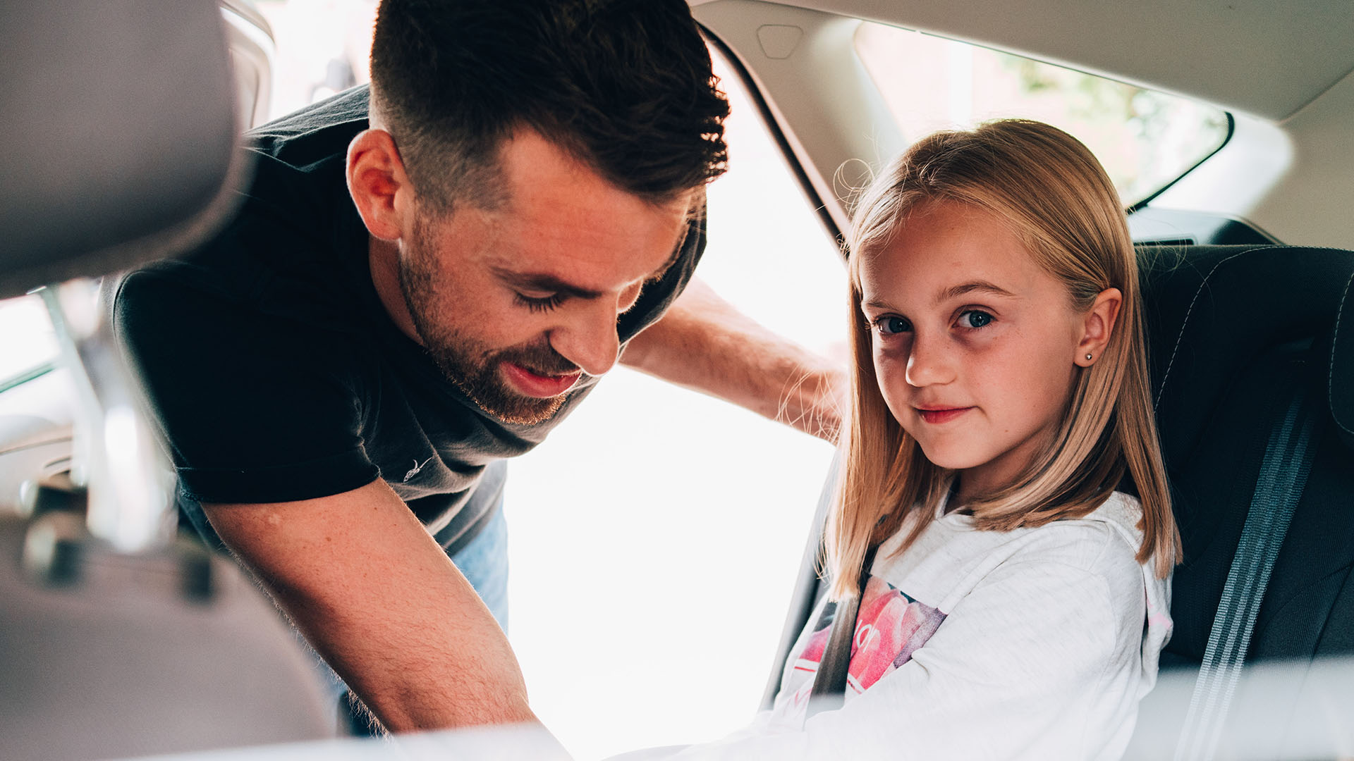 a man helping daughter with seat belt before driving off
