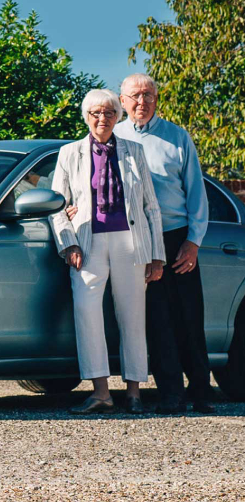 Mature driver standing beside their car