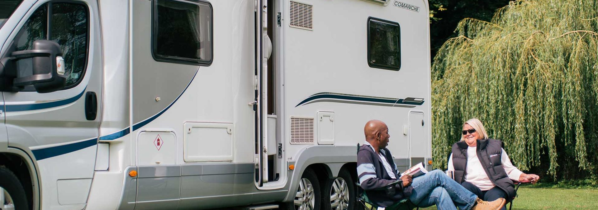 Motorhome and couple enjoying the piece of quiet of the countryside