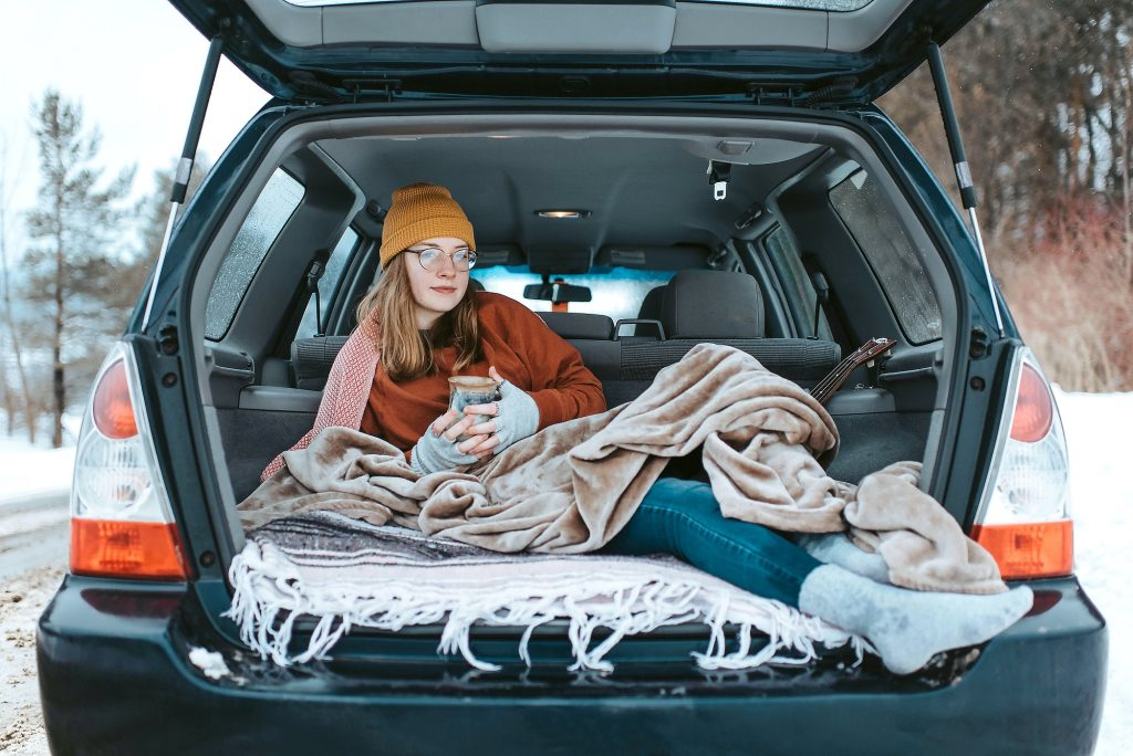 Person lying down in the back of the car with blankets